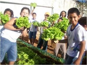 Crianças em horta escolar. Ao contrário dos alimentos vegetais, elas nunca terão aulas práticas de como produzir alimentos de origem animal. Pense nos motivos disso.