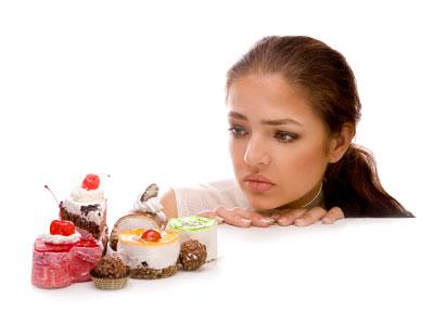 Moça desejando comer doces não veganos